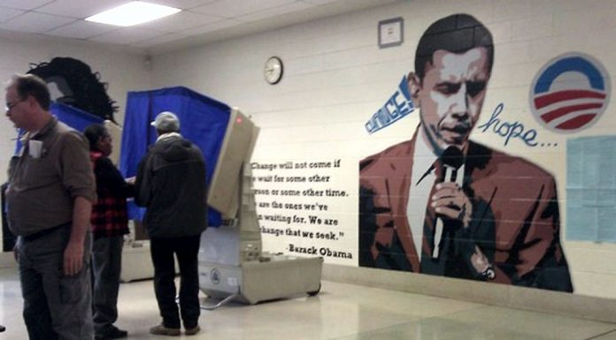 Giant Obama Mural on Polling Wall while voters vote.