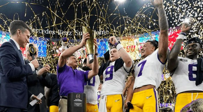 LSU head coach Ed Orgeron holds the trophy after their win against Clemson.