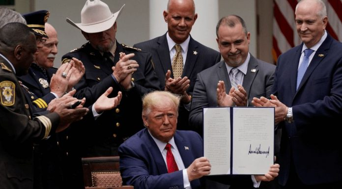 Law enforcement officials applaud after President Donald Trump signed an executive order on police reform.
