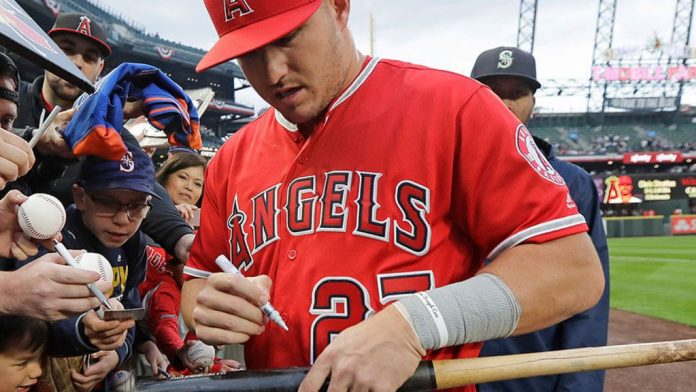 Los Angeles Angels center fielder Mike Trout autographs a bat