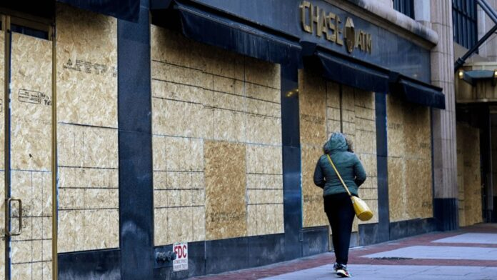 A woman walks past boarded-up businesses on the eve of the 2020 General Election