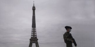 A French soldier patrols during the lockdown next to the Eiffel Tower