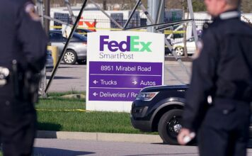 Police stand near the scene where multiple people were shot at the FedEx Ground facility